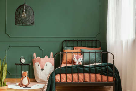 Copy space on empty dark green wall of trendy bedroom interior
