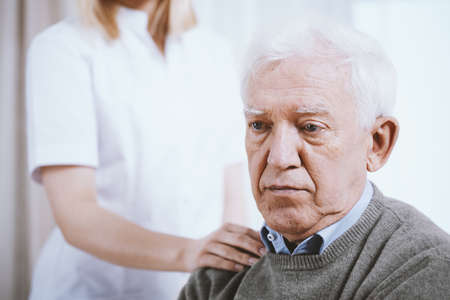 Portrait of senior man with hand of supporting nurse on his shoulder