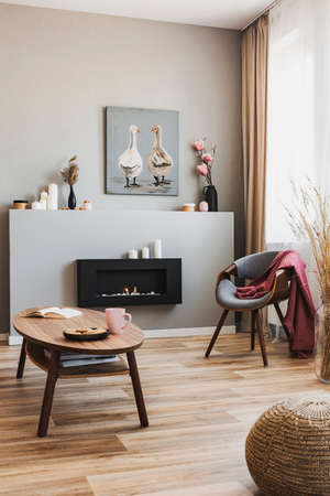 Cookies and pink team mug on wooden coffee table in grey living room interior with eco fireplace and chic chair Stock fotó