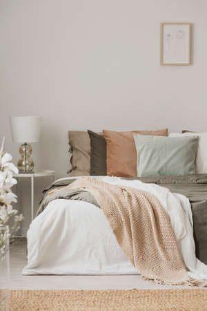 Earth colors in stylish bedroom interior with king size bed