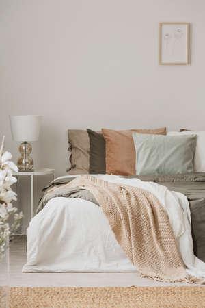 Colores tierra en el elegante interior del dormitorio con cama king size Foto de archivo