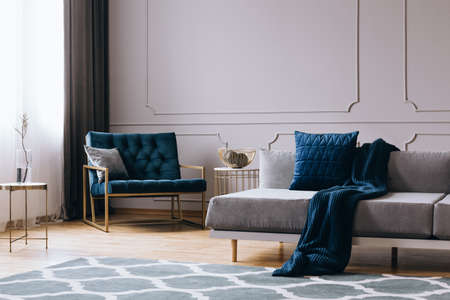 Pillows and blanket on modern sofa in bright living room interior