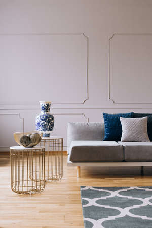 Grey couch with pillows in bright living room interior with hygge design