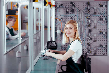 Profile view of concentrated young worker in denim overall working at factory