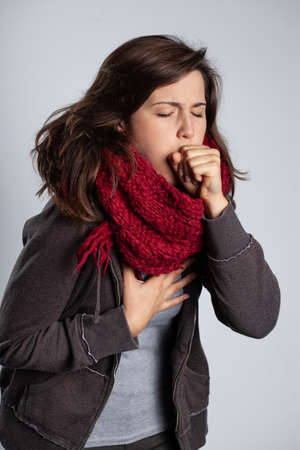 Young pretty brunette woman wearing jacket and scarf and coughing Фото со стока