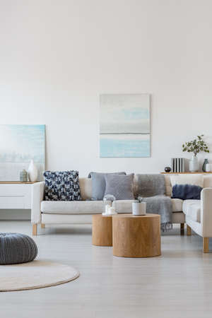 Two wooden coffee tables with plant in pot in front of grey corner sofa in fashionable living room interior Banco de Imagens
