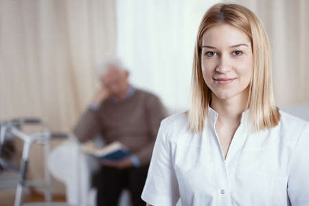 Beautiful young nurse with blonde hair and white uniform Stock Photo
