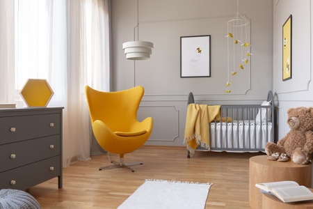 Trendy yellow egg chair in elegant grey nursery with wooden crib and posters on the wall Stock Photo