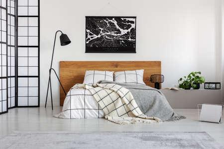 Black map on white wall above wooden headboard in simple bedroom interior Reklamní fotografie
