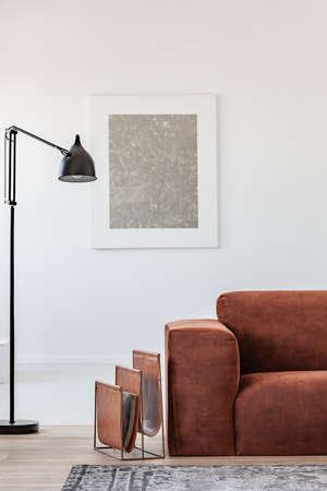 Black industrial lamp next to fashionable scandinavian sofa in bright living room interior Imagens