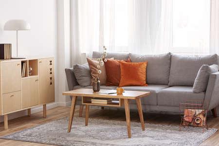 Retro wooden coffee table in front of grey couch in classy living room interior