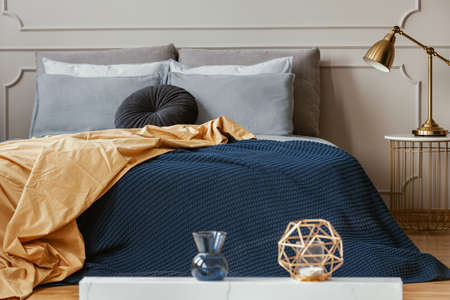 Golden lamp on trendy nightstand next to king size bed with comfortable bedding