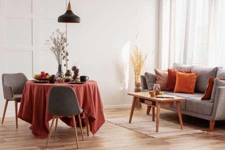 Interior de sala y comedor con diseño gris, blanco y jengibre