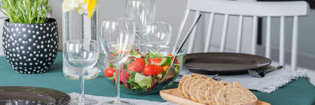 Close-up of wine glasses, salad and bread on a table in a dining room interior Stock Photo