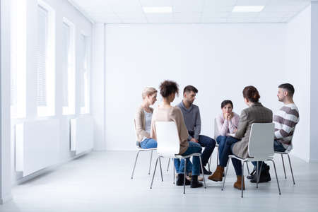 Female psychologist during meeting with a support group for workaholics, photo with copy space