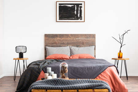 King size bed with orange and grey bedding between two wooden nightstand with lamp and vase