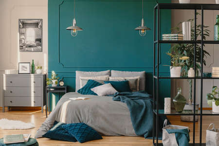 Two industrial lamps above comfortable double bed with cozy bedding, copy space on empty wall