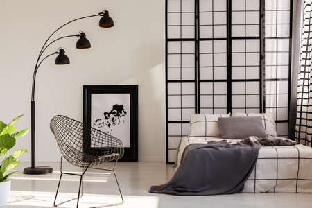 Fancy industrial armchair next to comfortable bed in bright interior