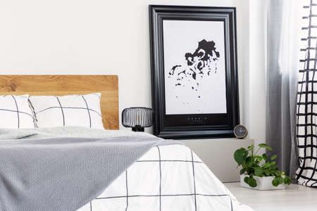 Black and white map in black frame in trendy bedroom interior with chequered bedroom Stockfoto