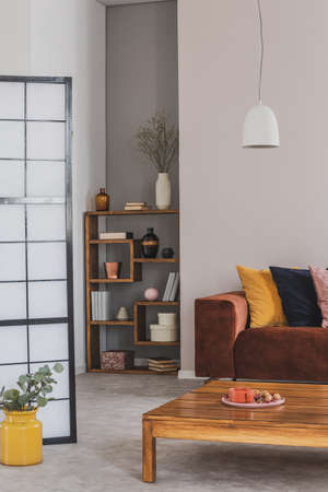 Yellow, black and pastel pink pillow on brown couch in grey living room interior, copy space on empty wall