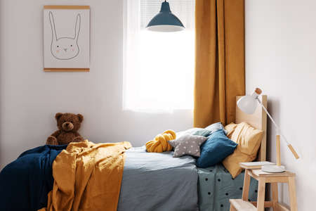 Stylish blue and orange kids bedroom design in bright apartment