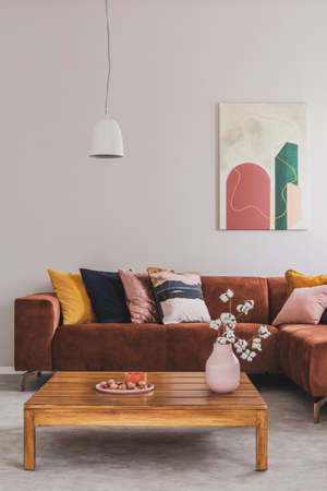 Flowers in vase on wooden coffee table in fashionable living room interior with brown corner sofa with pillows and abstract painting on the wall Stockfoto