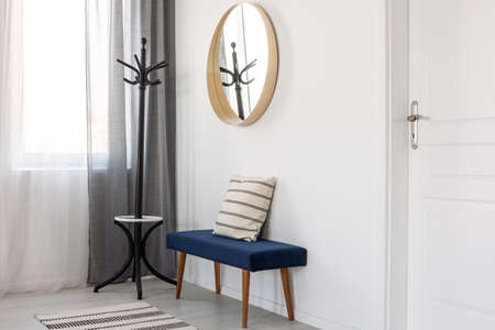 Round mirror in wooden frame on empty white wall of bright living room interior Stockfoto