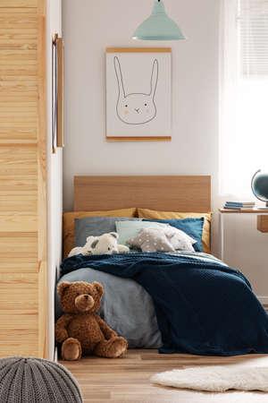 Brown cute teddy bear on wooden floor of stylish bedroom interior for kids Stockfoto