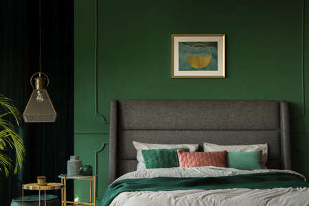 Stylish poster above comfortable king size bed with headboard in dark green bedroom
