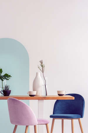 White vase on wooden table with fancy dining room interior with white and blue wall Stockfoto