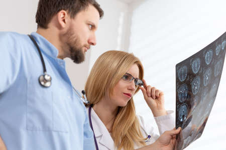 Young female doctor and handsome male nurse looking at x-ray exam