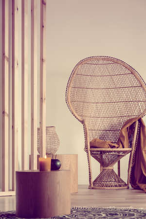 Fancy wicker peacock chair with blanket in trendy interior Stockfoto