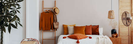 Pillow on a bed next to a ladder with hanging jumpers in a natural bedroom interior
