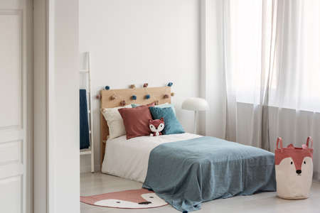 Bright bedroom interior with single bed with turquoise blanket on white bedding and colorful pillows and toy
