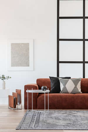 Stylish brown corner sofa with patterned pillows in elegant living room interior with mullions wall Stockfoto