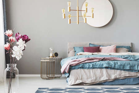 Golden chandelier above king size bed with blue, beige and pastel pink sheets Stockfoto