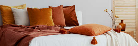 Decorative pillow on a bed in a natural bedroom interior