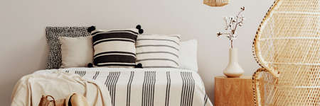 Striped sheets on a bed in a natural bedroom interior