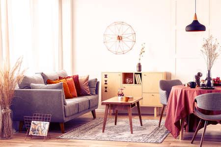 Stylish modern clock on white wall of trendy living room interior