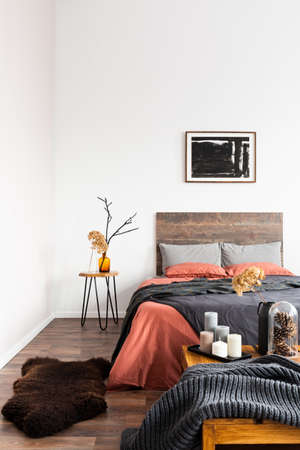 Back poster on the white wall of elegant bedroom interior with king size bed with wooden headboard Stockfoto