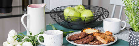 Close-up of apples and cookies on a table in a dining room interior