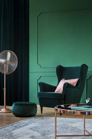 Emerald green velvet armchair with pastel pillow in trendy living room interior with copper accents Stockfoto