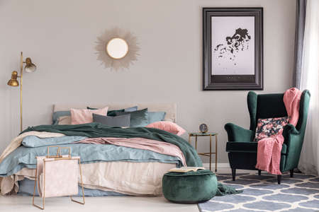 Emerald green armchair with floral pillow and pastel pink blanket in trendy bedroom interior Stockfoto