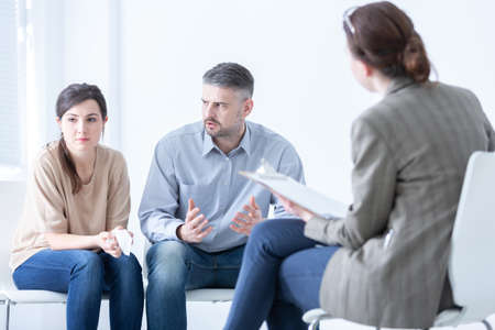 Married couple with problems during a therapy session with professional psychologist