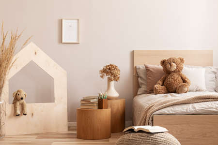 Elegant kids bedroom with wooden furniture and toys, real photo with copy space on empty wall