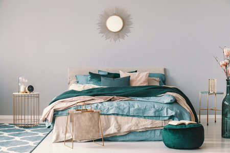 Clock and flower in fancy vase on nightstand table next to king size bedroom with emerald green and beige bedding