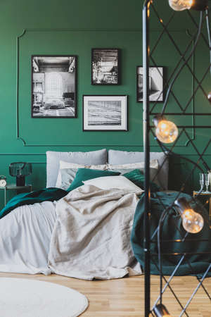 Green wall with gallery of poster in trendy bedroom interior with double bed