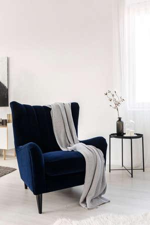 Dark blue velvet wing back chair with grey blanket in trendy living room