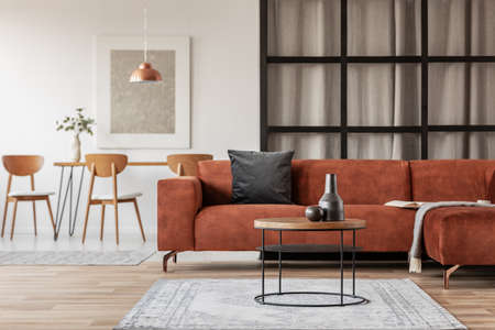Silver abstract painting in white frame on the wall of trendy living room interior with brown corner sofa