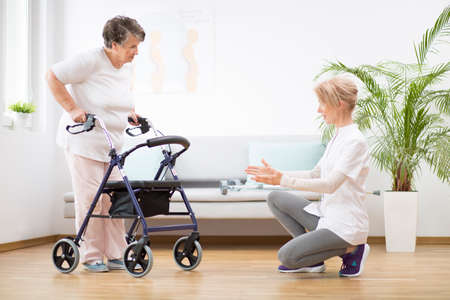 Senior woman with walker trying to walk again and helpful physiotherapist supporting her
